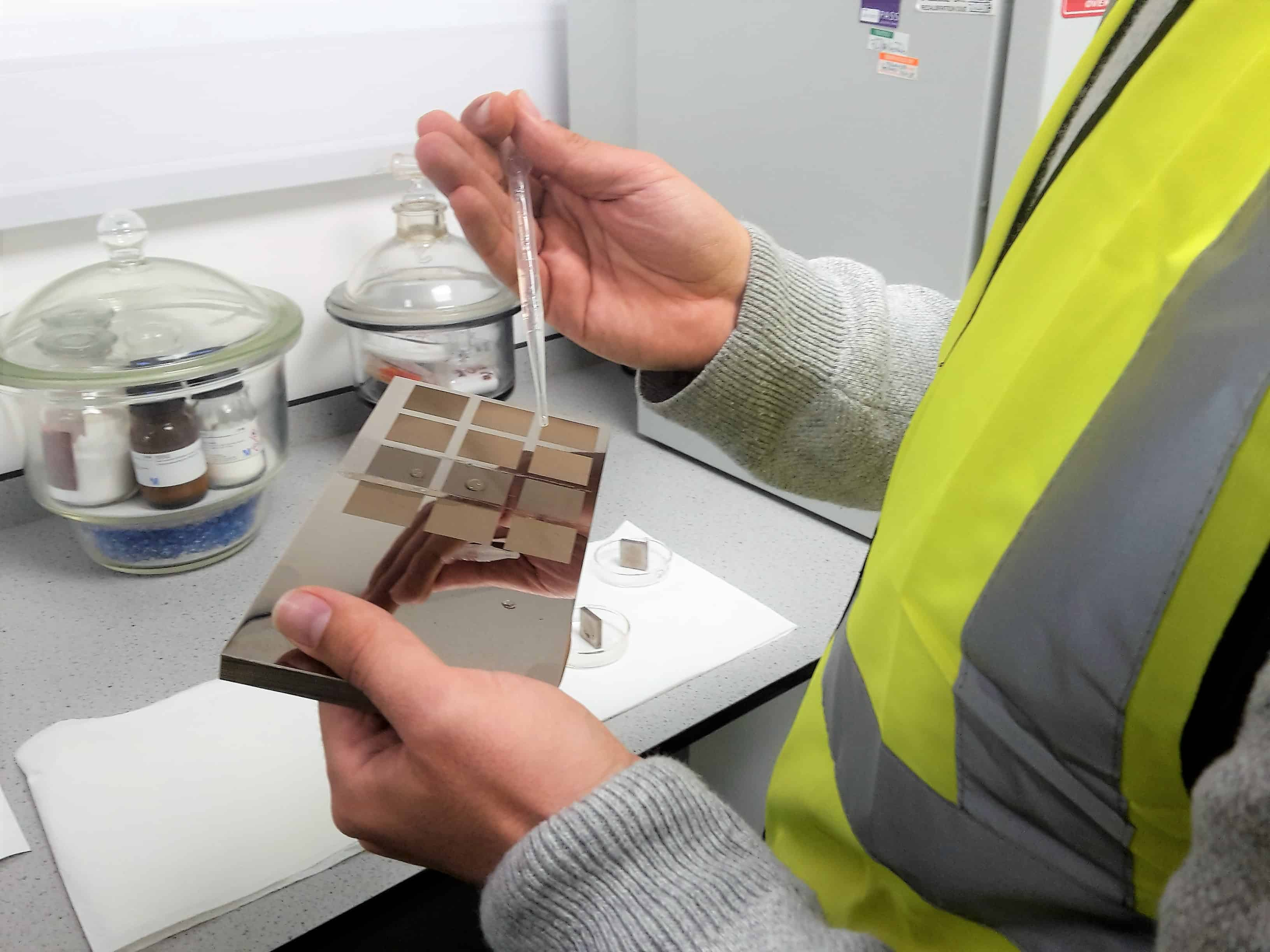 Man in high-vis jacter using a pipette to drop a formula onto a testing plate