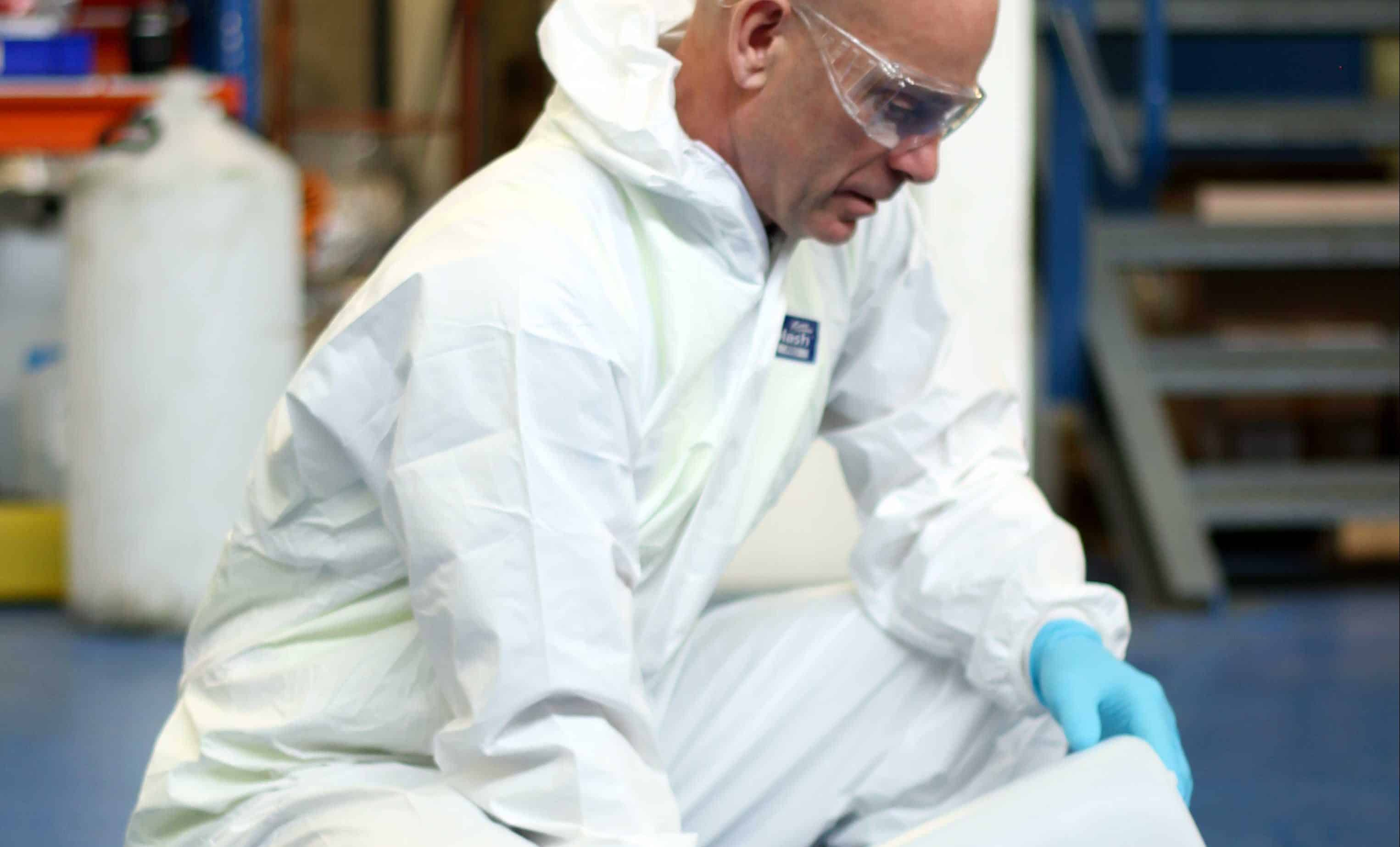A cleanroom operator dressed in a white jumpsuit, wearing blue protective gloves and clear goggles