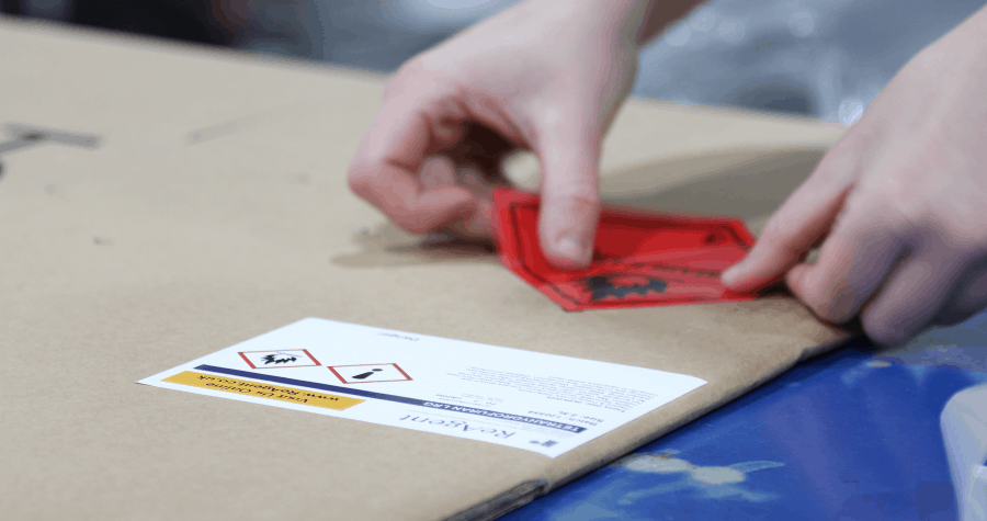 Close up of anonymous hand putting flammable hazard label on cardboard box