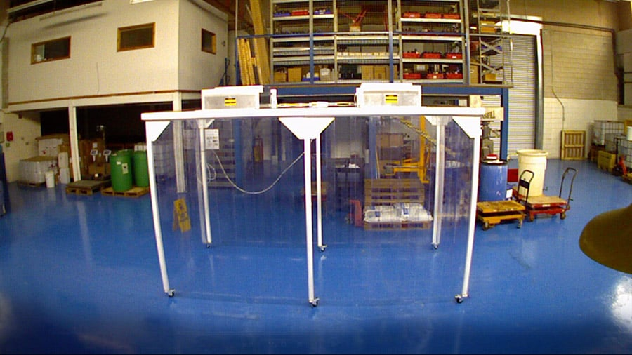 A photo of a small cleanroom with clear walls and a white support beams
