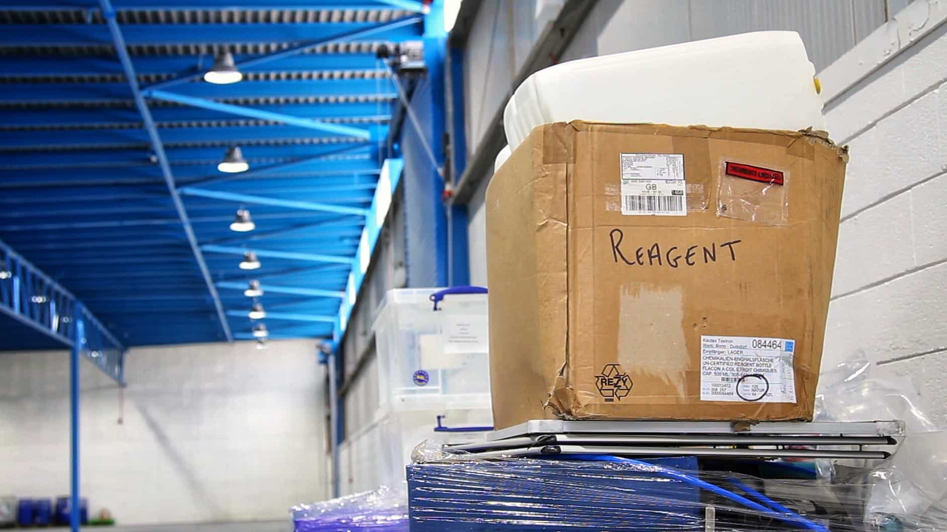 A cardboard moving box with 'ReAgent' written on it; a factory is behind it.