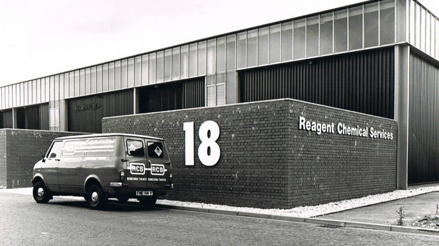 Old black and white photo showing a van parked outside ReAgent's factory